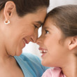 Profile of mother and daughter touching noses - Stock Photo