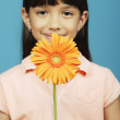 Girl holding flower in front of face - Stock Photo