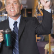 Mature businessman on subway with coffee — Stock Photo