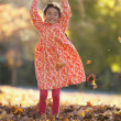 Young girl playing in pile of leaves - Stock Photo