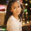 Hispanic girl in front of Christmas tree — Stock Photo