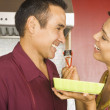 Hispanic couple eating sushi in kitchen — Stock Photo