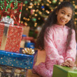 Girl next to stack of gifts on Christmas - Stock Photo