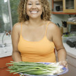 Young woman holding a plate of spring onions — Stock Photo