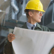Businessman in hard hat holding blueprints - Stock Photo