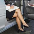 Eurasian businesswoman working in car — Stock Photo