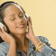 Studio shot of a Dominican woman listening to music on headphones — Stock Photo