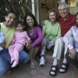 Hispanic family sitting on steps smiling — Stock Photo #13234911
