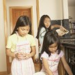 Three young Asian sisters doing the dishes - Stock Photo