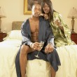 Stock Photo: Couple in robes with champagne in bedroom