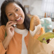 Young woman talking on her cell phone while holding a bag of groceries — Stock Photo #13234938