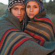Portrait of couple in caps wrapped in a blanket — Stock Photo