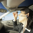 Businesswoman driving and putting on makeup — Stockfoto