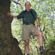 Senior Hispanic man standing in tree - Photo