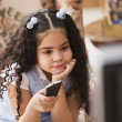 Bored young girl watching television — Stock Photo