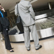 Businesspeople waiting for luggage at airport — Stock Photo
