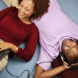 Couple laying on floor with headset and laptop — Stock Photo