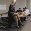 Businesswoman sitting on conference table — Stock Photo