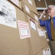 Businessman in warehouse looking at returned packages — Stock Photo