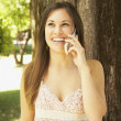 Hispanic woman talking on cell phone outdoors — Stock Photo #13235096