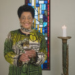 Stock Photo: Senior African woman holding goblet in church