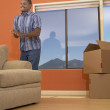 Man standing by couch - Stock Photo