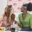 Stock Photo: Two women singing to headphones