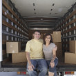 图库照片: Portrait of couple sitting in moving truck