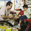 Young Hispanic boy trying shoes at shoe store - Stock Photo