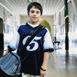 Portrait of boy holding bag in school hallway - Stock Photo