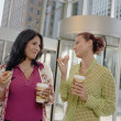 Businesswomen eating donuts — Stock Photo