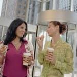 Businesswomen eating donuts — Stock Photo
