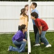 Foto Stock: Mixed Race children looking at each other through fence
