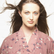 Portrait of woman wearing kimono with hair blowing - Stock Photo