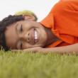 Portrait of boy laying on grass - Stock Photo