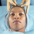 Gloved hands tying wrap on African American woman&#039;s head in hospital bed - Stock Photo