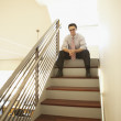 Businessman sitting at the top of a staircase - Stockfoto