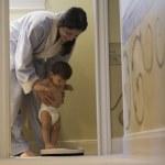 Hispanic mother holding baby on adult scale — Stock Photo