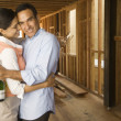 Hispanic couple hugging with champagne at construction site - Stock Photo