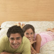Portrait of couple laying on bed - Stock Photo