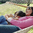 Stock Photo: Mother and daughter relaxing in a hammock