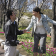 Asian couple laughing and holding hands in urban park - Stock Photo