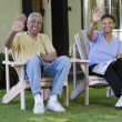 Middle aged couple waving from their lawn chairs - Stock Photo
