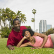 African couple laying in grass smiling — Stock Photo
