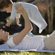 Hispanic mother lying on the grass holding baby above her - Stock Photo