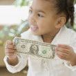 African girl holding dollar bill - Stock Photo