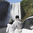 Couple in winter clothes looking at waterfall — Stock Photo