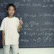 Portrait of boy holding chalk standing in front of chalkboard - Stock Photo