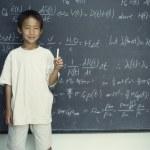 porträtt av pojke håller krita stående framför svarta tavlan — Stockfoto
