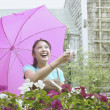 Royalty-Free Stock Photo: Asian woman with umbrella holding mug out in rain
